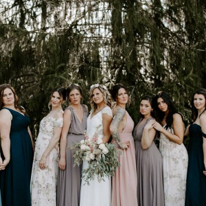 Bridesmaids in mismatched dresses of teal, blush, and beige