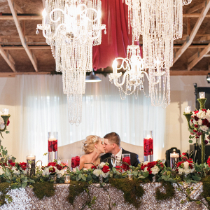 Couple sitting at sweetheart table with crystal chandeliers above
