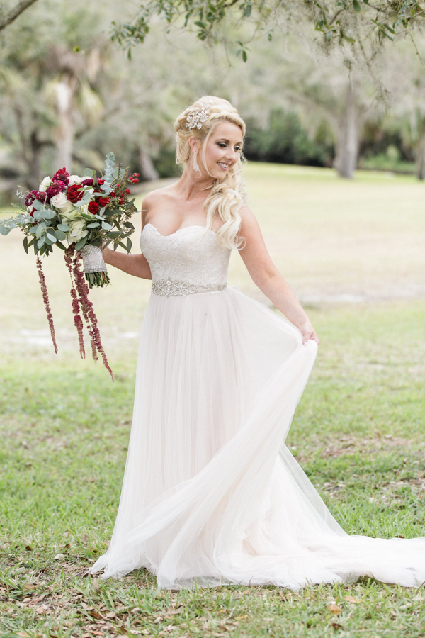 bride holding garden style red rose bouquet