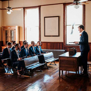 Groom talking to groomsmen in old style classroom