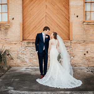 bride and groom standing in front of brick wall