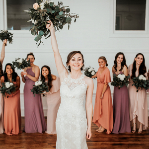 Bride holding bouquet in front of bridesmaids wearing miss matched dresses
