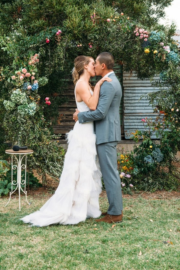 Newlyweds First Kiss Under Floral Arch
