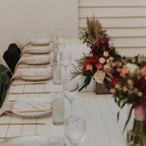 Wedding reception with long table and red florals