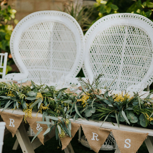 Sweetheart table with pennants and peacock chairs