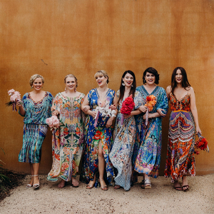 Bridesmaids in mismatched colorful print dresses