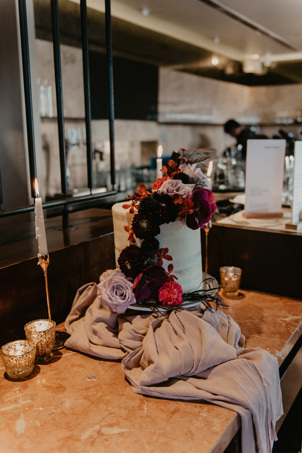 Modern romantic wedding cake with cascading fresh florals