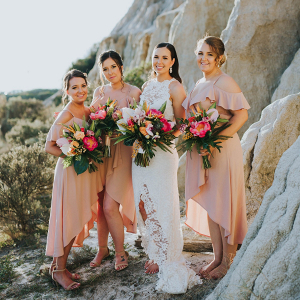 Bridesmaids in peach high-low gowns
