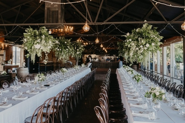Wedding reception with long tables and suspended florals