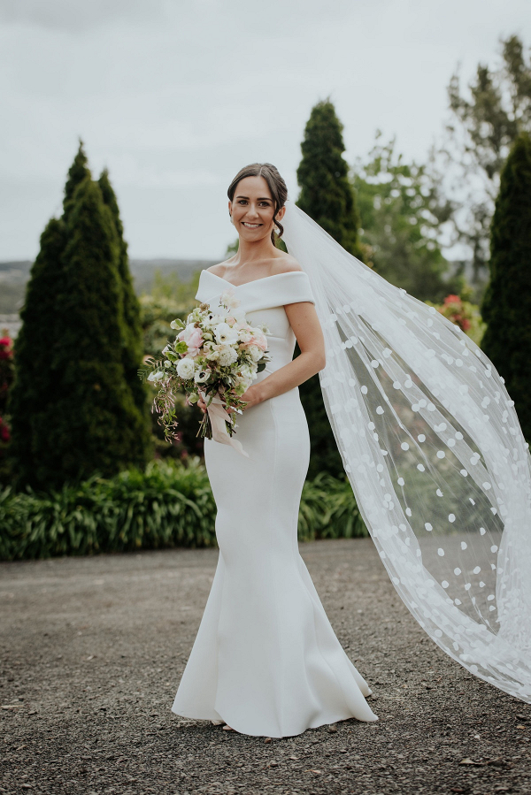 Off the shoulder wedding gown with polka dot veil