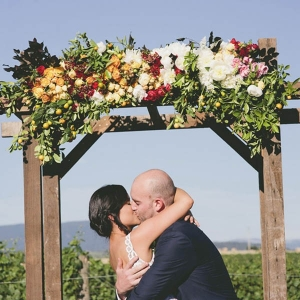 Newlyweds Kissing Under Floral Arch