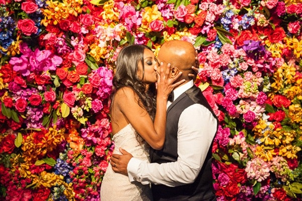 Newlyweds With Bright Floral Wall