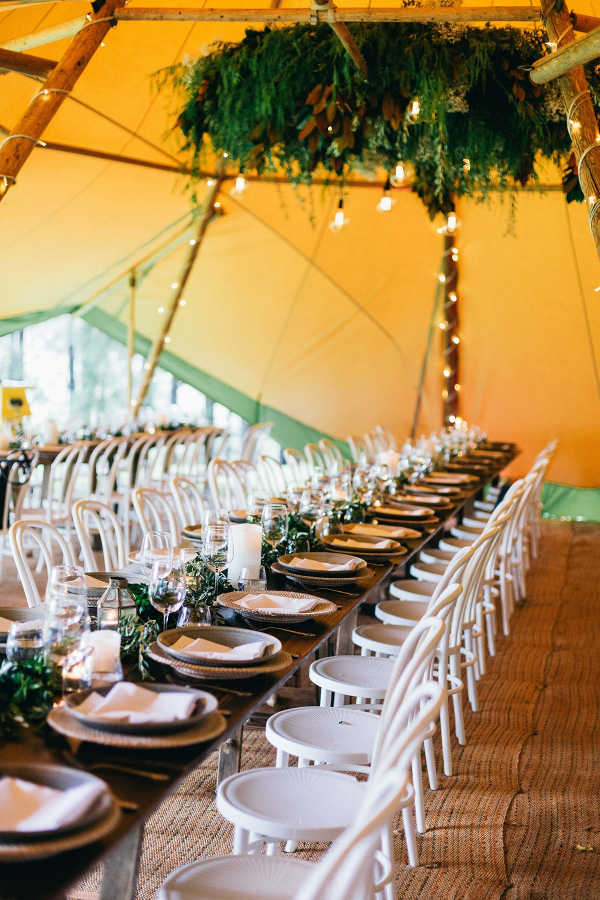 Long table tented wedding reception with suspended greenery