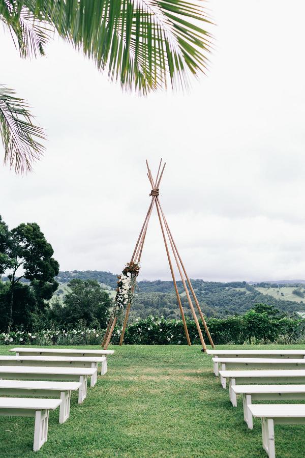 Outdoor wedding ceremony with boho backdrop
