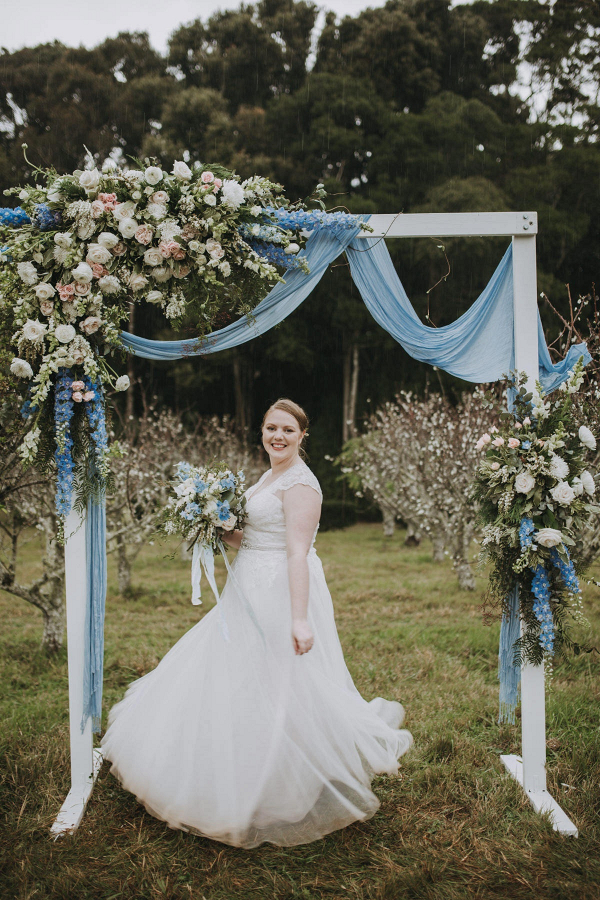 Lush floral and draping ceremony arch