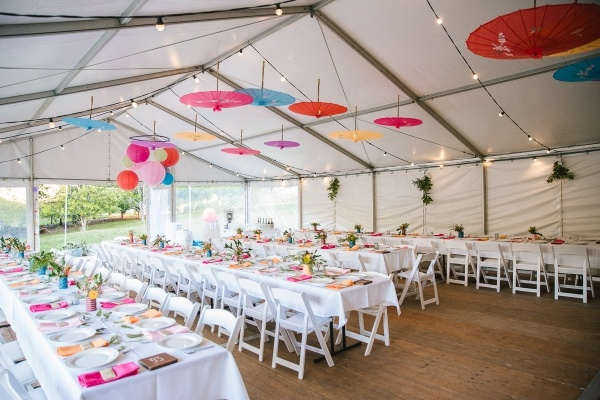 Colorful tented wedding reception with hanging umbrellas