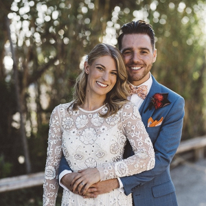 Bride in beaded long sleeve gown with groom in blue gray suit