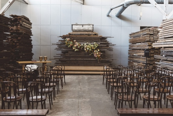 Industrial ceremony backdrop with wood planks and floral installation