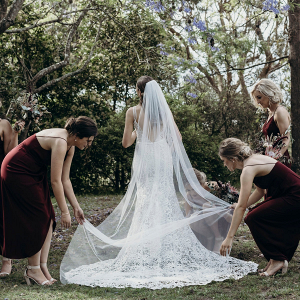 Bridesmaids helping straighten veil
