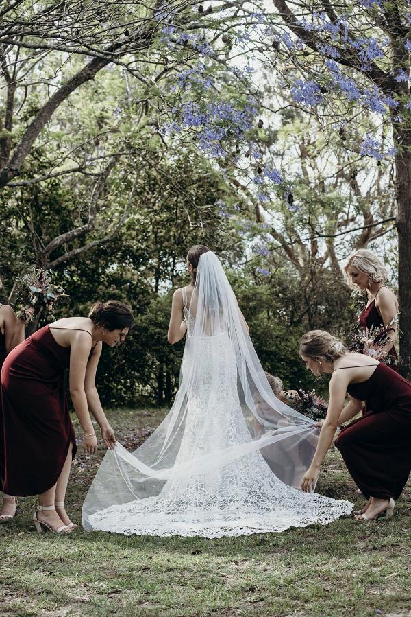 Bridesmaids helping straighten veil