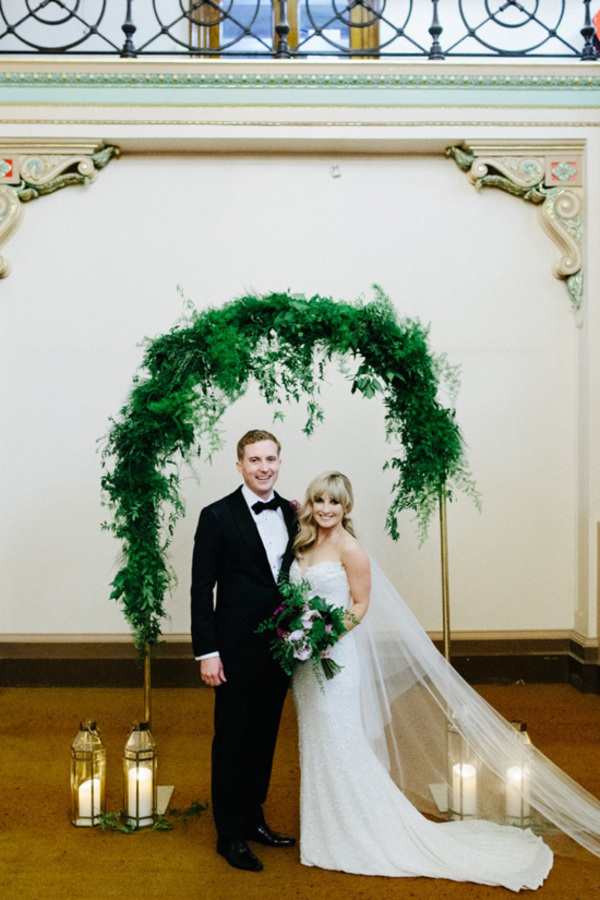 Newlyweds With Greenery Arch