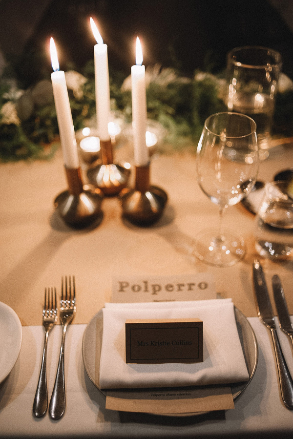 Modern wedding place setting with candles and greenery