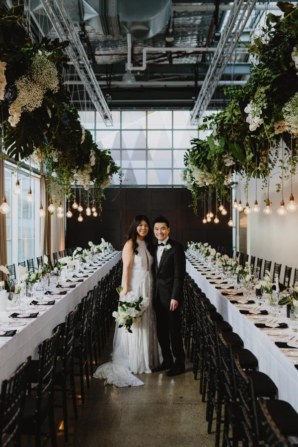 Modern black and white wedding reception with hanging greenery