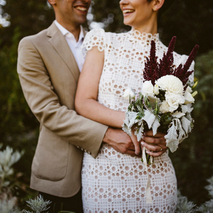 Bride in modern lace dress with small bouquet