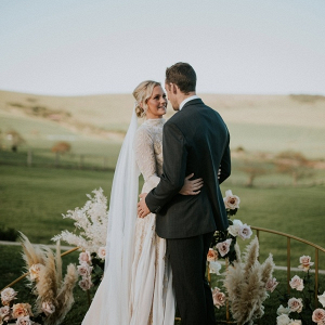 Outdoor wedding ceremony with semi circle floral backdrop