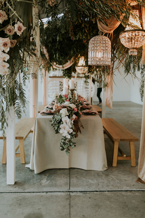 Boho wedding table with hanging greenery and chandeliers