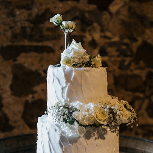 White buttercream wedding cake with fresh flowers