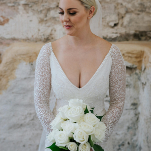 Bride in beaded wedding dress with classic white rose bouquet