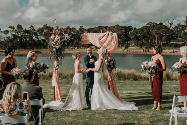 Outdoor wedding ceremony with draping and floral covered arch