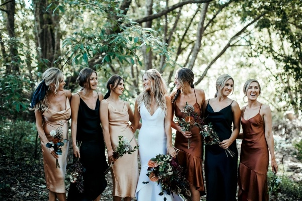 Bridesmaids in mismatched dresses of bronze, gold, and black