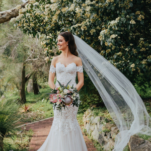 Bride in off the shoulder lace gown with cathedral veil