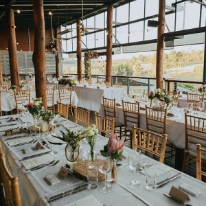 Wedding reception with long tables and protea floral centerpieces