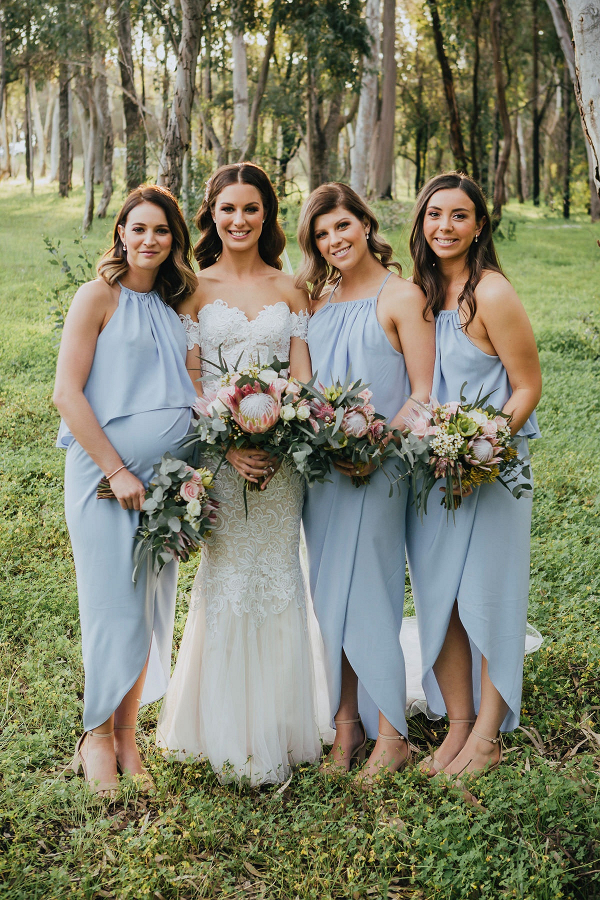 Bridesmaids in light blue gowns and protea bouquets