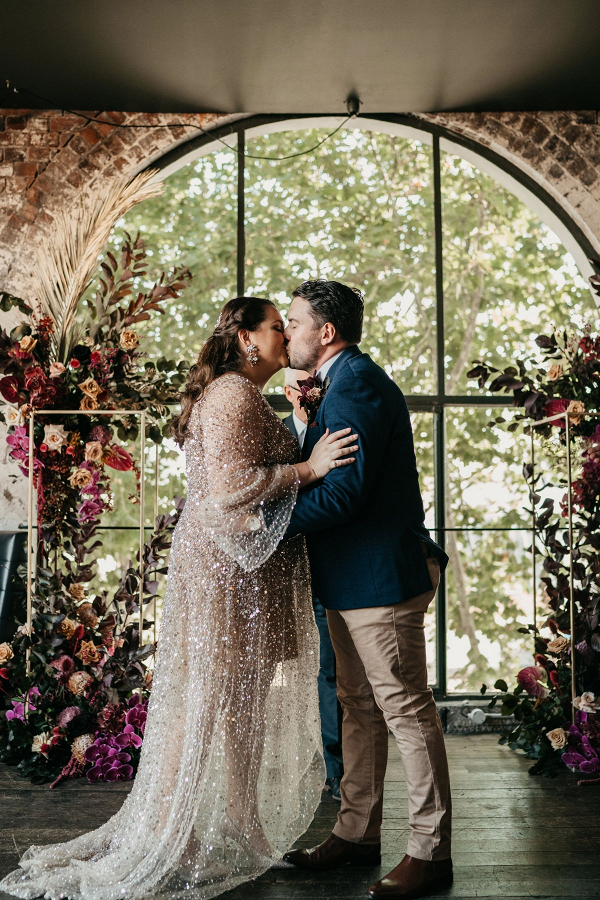 Boho modern wedding ceremony with lush floral backdrop and sparkle wedding dress