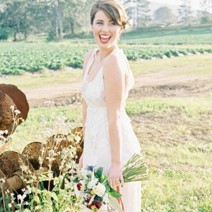 Bride in Strawbwerry Field With Red Bouquet