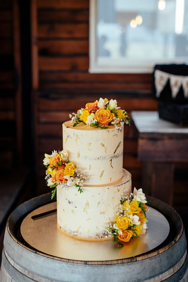 Gold leaf wedding cake with yellow flowers