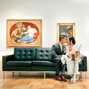 The couple siting on green couch with pictures hanging in the back
