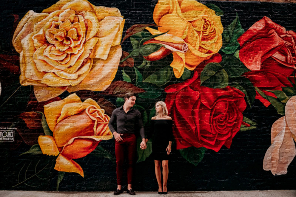 In front of a flower mural