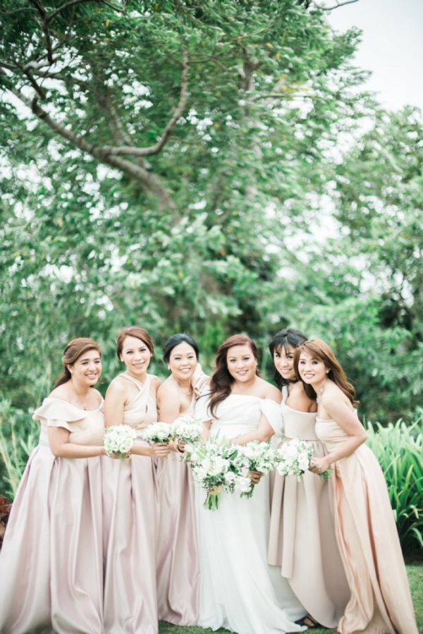 plus size bride in off the shoulder gown with bridesmaids wearing blush