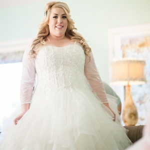 Plus Size Bride wearing a ruffled wedding dress with sheer sleeves