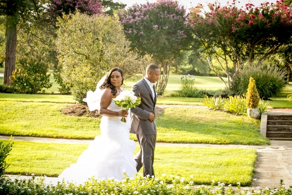 plus size bride in mori lee walking with her groom