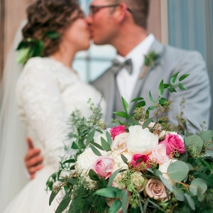 Gorgeous portrait of a bride and groom, kissing behind her amazing bouquet!
