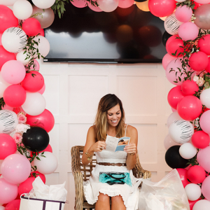 Beautiful bride, opening her bridal shower presents surrounded by balloons!