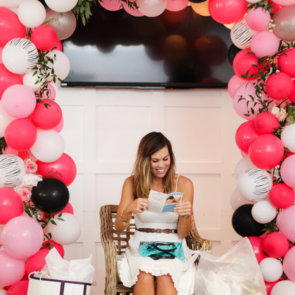 beautiful bride opening her bridal shower presents surrounded by balloons