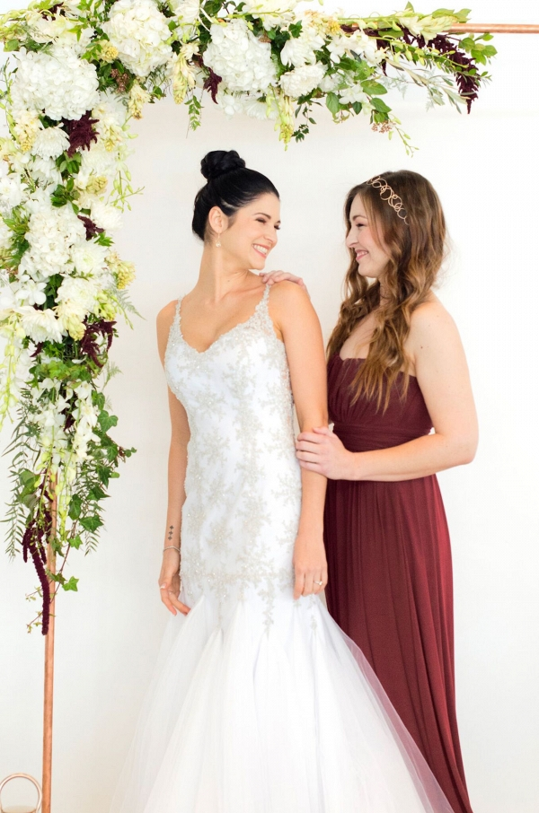 Bride & Bridesmaid with Copper Floral Ceremony Arch