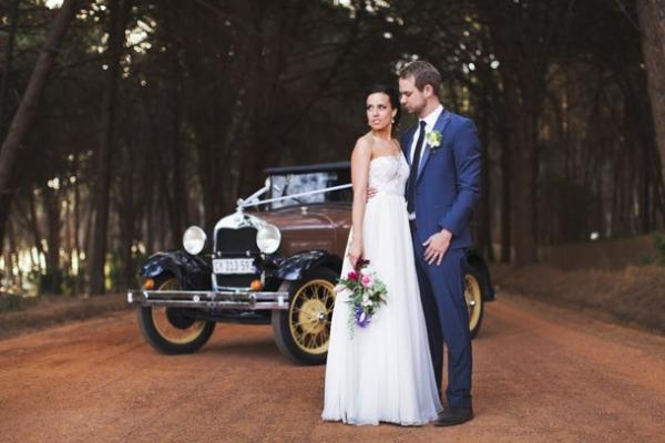 Bride & groom with vintage car